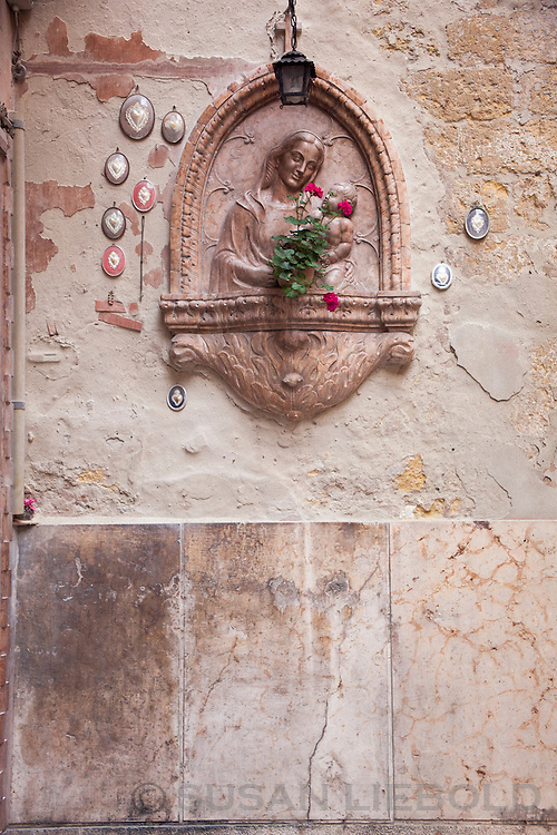 A wall decoration of Mary holding Jesus, in Verona, Italy.