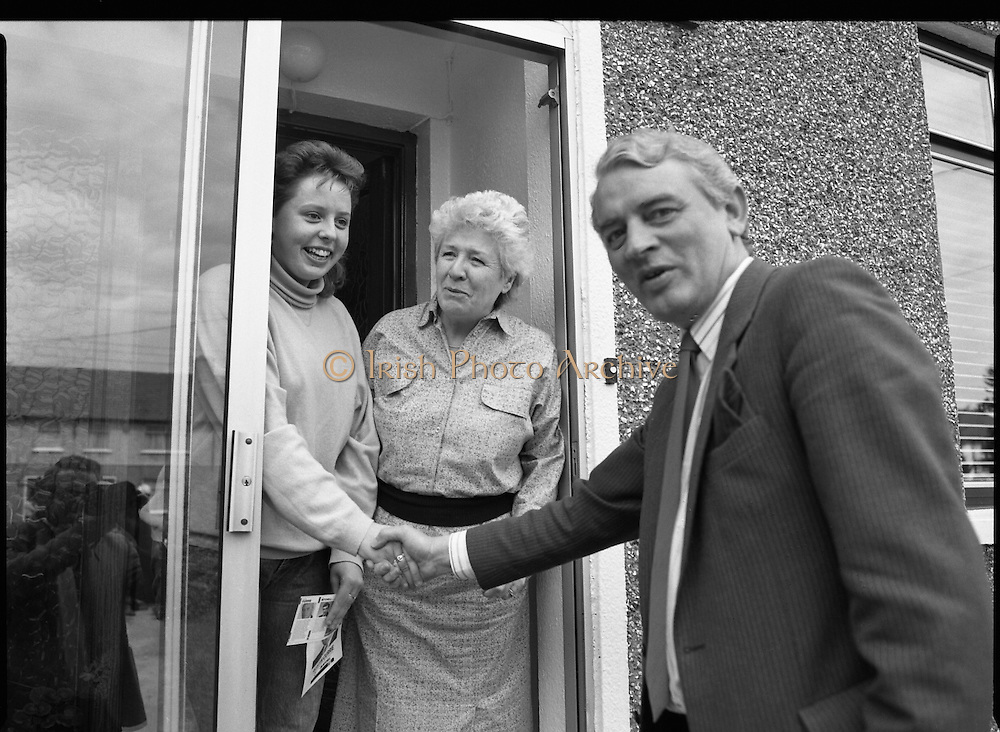 Austin Currie Canvas In Palmerstown (T1)..1989..07.06.1979..06.07.1989..7th June 1989..In the general election The Fine Gael Party chose Mr Austin Currie to contest for a seat in Dail Eireann. Well known as a civil rights activist and peace campaigner Mr Currie hoped to win a seat alongside running mate Mr Jim Mitchell.Mr Currie previously held a seat in the Northern Ireland Executive and held a position as Minister for Housing and Local Planning. Mr Currie is a founder member of the S.D.L.P...Mr Currie is pictured with two potential voters as he hits the campaign trail in Palmerstown, Dublin.