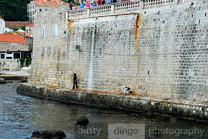 Woman and dog walking at base of stone wall opposite Fortress Bokar, Dubrovnik old town, Croatia