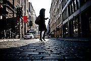 Back-lightened silhouette of a girl walking on the pavement of Greene Street in SoHo, Manhattan, New York, 2009.