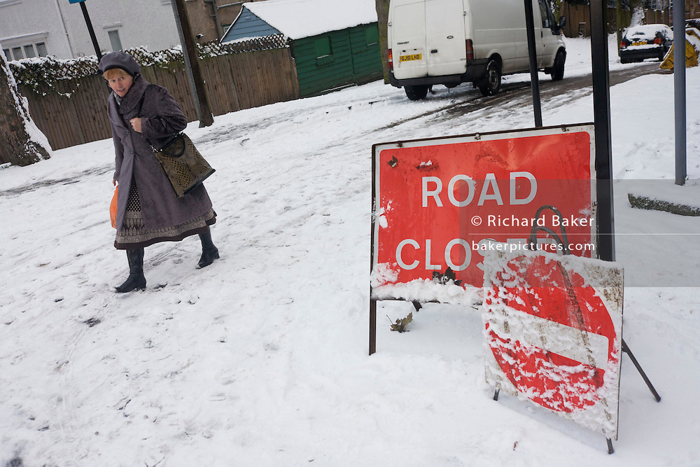 A Closed Road sign and a local lady shopper passes-by on a hill in south London during wintry snows.