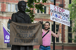 London, UK. 24th July, 2021. A LGBTI+ protester holds a sign alongside the statue of Millicent Fawcett in Parliament Square before the first-ever Reclaim Pride march. Reclaim Pride replaced the traditional Pride in London march, which many feel has become too commercial and strayed from its roots in protest, and was billed as a People's Pride march for LGBTI+ liberation.