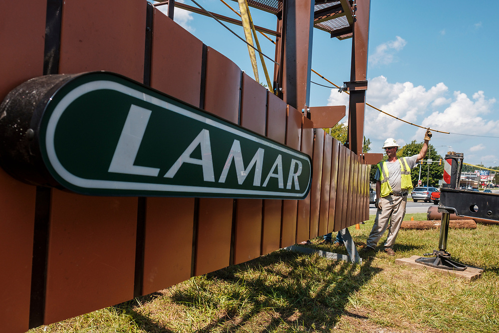 Rick Handy, with arm raised, gives directions to the crane operator while lifting the support structure while technicians from Lamar Advertising install a digital billboard structure along Wards Road in Lynchburg, VA Wednesday, August 29, 2018. U.S. companies are investing in re-training efforts to fill a slew of open positions as a tight labor market and changing job requirements makes it hard to find qualified staffers.<br /> CREDIT: Justin Ide for The Wall Street Journal<br /> RETRAIN