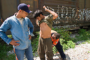 07 OCTOBER 2003 -- TAPACHULA, CHIAPAS, MEXICO:  Border crossers from Central America are searched by a Mexican Grupo Beto officer in the train yards in the Mexican town of Hidalgo, near Tapachula, hoping to hop the freight trains north on their way to the US. Tapachula is center of the smuggling industry between Mexico and Guatemala. Consumer goods are smuggled south to Guatemala (to avoid paying Guatemalan import duties) and people are smuggled north into Mexico. Most of the people coming north are hoping to eventually get to the United States. PHOTO BY JACK KURTZ