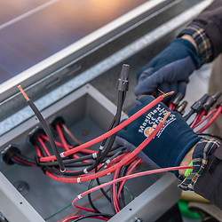 A PV Squared employee wiring a solar panel installation on the roof of a commercial building in Greenfield, Massachusetts.