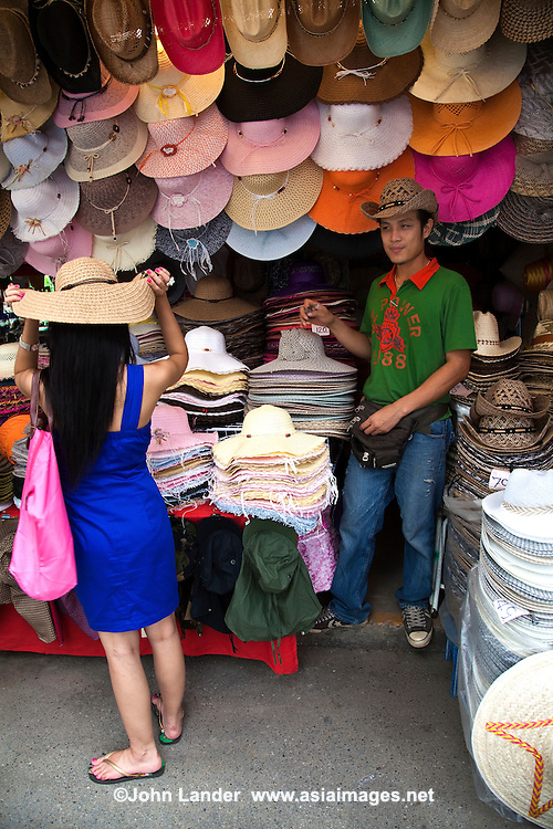 Hatter at Chatuchak Market - Chatuchak Market or sometimes written Jatujak or Weekend Market in Bangkok is the largest market in Thailand, and one of the largest of the world. Frequently called J.J. it covers over 35 acres and contains more than 5,000 stalls not counting wandering vendors and street entertainers. It is estimated that the market receives between 200,000 and 300,000 visitors each day. Most stalls are only open on Saturdays and Sundays. The market offers a wide variety of products including household items, clothing, Thai handicrafts, religious artifacts, collectibles, foods, and even live animals.