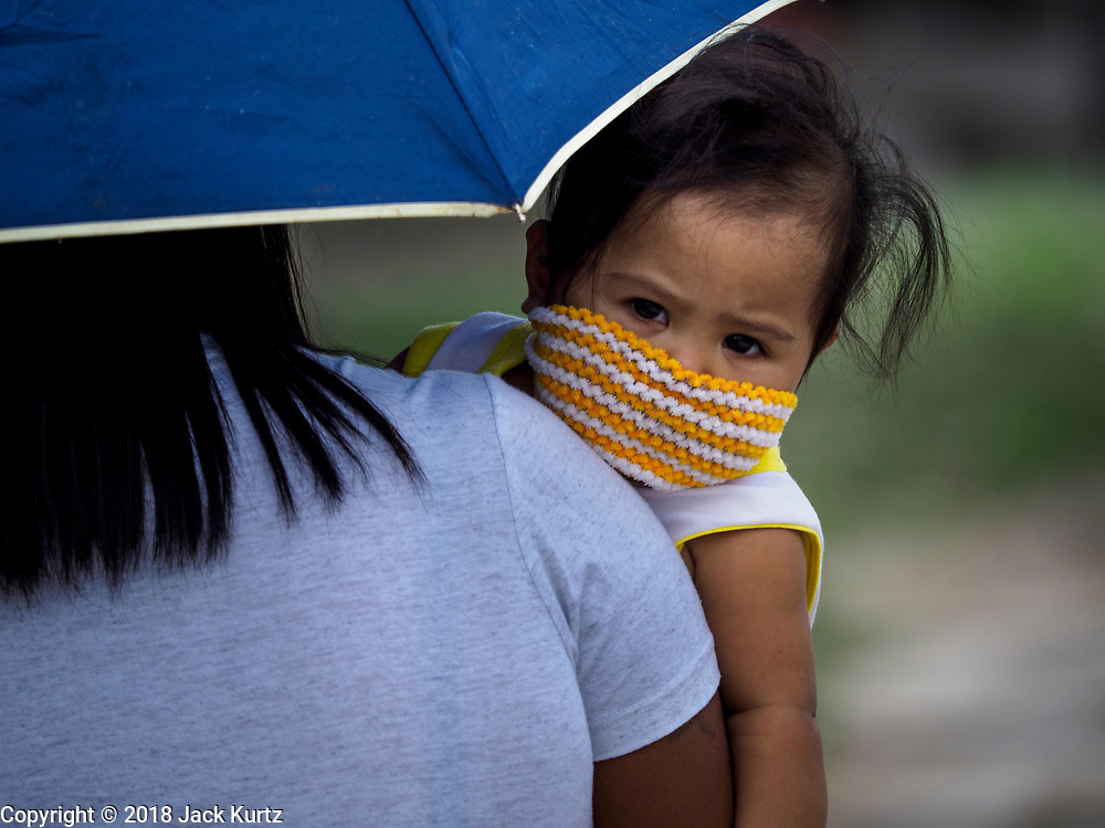30 JANUARY 2018 - GUINOBATAN, ALBAY, PHILIPPINES:  A girls wearing a knitted face mask during an ash fall in Guinobatan. Mayon volcano continued to erupt but not as dramatically as it did last week. The small eruptions are still sending ash clouds over communities west of the volcano and the government is encouraging people to stay indoors, wear face masks and avoid strenuous activities when ash is falling.    PHOTO BY JACK KURTZ