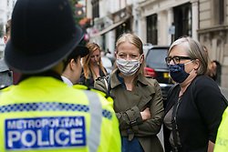 London, UK. 23rd August, 2021. Acting Green Party leader Sian Berry and Green Party London Assembly Member Caroline Russell speak to Metropolitan Police officers operating a cordon around environmental activists from Extinction Rebellion in the Covent Garden area during the first day of Impossible Rebellion protests. Extinction Rebellion are calling on the UK government to cease all new fossil fuel investment with immediate effect. Credit: Mark Kerrison/Alamy Live News