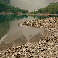 Hikers stand beside Moraine Lake in Banff National Park, Alberta, Canada.