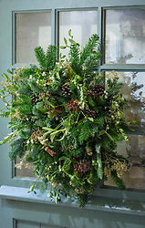 Natural Christmas wreath.  Decorations include mistletoe, pine cones, box, green and blue spruce, golden sprayed gypsophila and cinnamon sticks