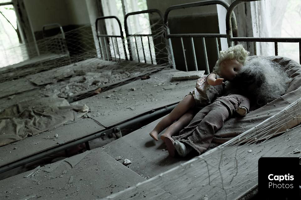 Dolls on a bed in an abandoned school house near Chernobyl, Ukraine.