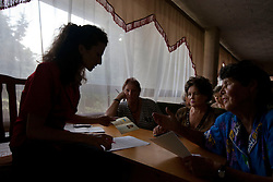 Miroslava Prymak, an attorney helps, left to right, Galina Kukharchuk, Nadia Vatorska and Nadia Kalinchenko during a Òspecial consultationÓ for potential clients who are children of the Second World War, Rivne, Ukraine, June 15, 2011. This vulnerable group is made up of seniors, most of whom are not receiving proper compensation as promised by the government. The legal team advises them on how to properly fill out forms and submit them to the courthouse, while encouraging them not to give up on their rights. More than half of the worldÕs population, four billion people, live outside the rule of law, with no effective title to property, access to courts or redress for official abuse. The Open Society Justice Initiative is involved in building capacity and developing pilot programs through the use of community-based advocates and paralegals in Sierra Leone, Ukraine and Indonesia. The pilot programs, which combine education with grassroots tools to provide concrete solutions to instances of injustice, help give poor people some measure of control over their lives.