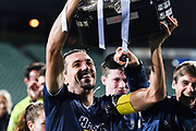 Auckland City FC captain Angel Berlanga celebrates with the Premiership Trophy after his teams win against Team Wellington.<br />