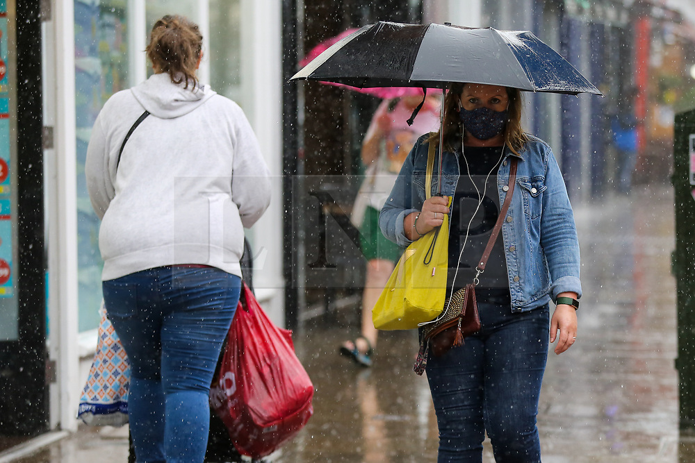 © Licensed to London News Pictures. 10/09/2021. London, UK. A woman shelters from the rain underneath an umbrella in north London, as wet weather conditions continue after a recent mini heatwave in London. Photo credit: Dinendra Haria/LNP