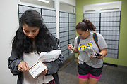 Sabrina Villanueva, left, opens a package at the campus post office at the University of Rochester in Rochester, New York on August 31, 2016. Villanueva earned 12 credits through a community college while in high school in Dallas, but the University didn't accept them, causing her to pursue a minor in Spanish rather than sociology or psychology as she had originally intended.