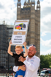 © Licensed to London News Pictures. 20/07/2020. London, UK. Justin Scott and his son Harry 6 from Manchester hold a placard during a coach demonstration in Parliament Square. The demonstration by 500 coaches took place in Westminster including driving around Parliament Square asking government for more help for the coach industry. Last week, Prime Minister Boris Johnson urged Britons to return back to working in offices to help service industries and the economic recovery. Photo credit: Alex Lentati/LNP