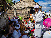 20 JULY 2016 - KUSAMBA, BALI, INDONESIA:  A Hindu priest sprinkles holy water on people gathered on Kusamba beach for a ceremony. Several hundred Balinese Hindus gathered on the beach in Kusamba, Bali, for a ceremony to honor the full moon. They prayed for more than hour and then community leaders threw an offering into the ocean.      PHOTO BY JACK KURTZ