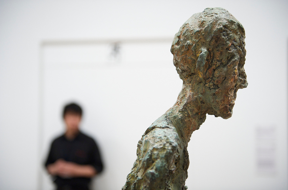 London.  September 30, 2008.  A museum goer admires a Giacometti sculpture, 'Walking Man I,' from the Miro, Calder, Giacometti, Braque exhibition at the Royal Academy of Arts.  The show opens on October 4 and runs until January 2, 2009.
