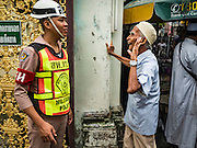 06 JULY 2016 - BANGKOK, THAILAND:  An elderly Muslim man chats with a Thai military policeman stationed in front of Ton Son Mosque for Eid services. Eid al-Fitr is also called Feast of Breaking the Fast, the Sugar Feast, Bayram (Bajram), the Sweet Festival or Hari Raya Puasa and the Lesser Eid. It is an important Muslim religious holiday that marks the end of Ramadan, the Islamic holy month of fasting. Muslims are not allowed to fast on Eid. The holiday celebrates the conclusion of the 29 or 30 days of dawn-to-sunset fasting Muslims do during the month of Ramadan. Islam is the second largest religion in Thailand. Government sources say about 5% of Thais are Muslim, many in the Muslim community say the number is closer to 10%.       PHOTO BY JACK KURTZ