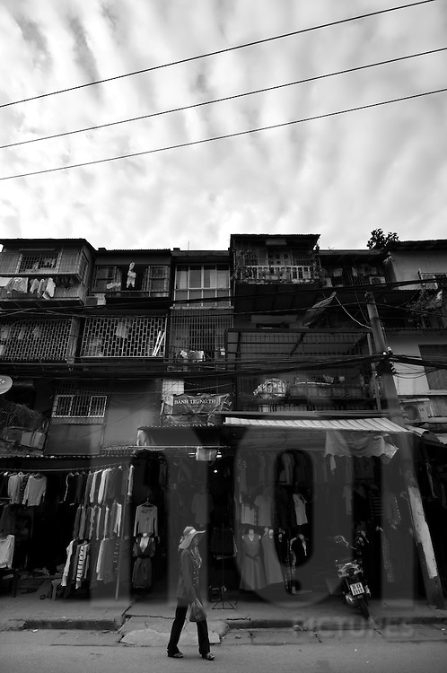 A woman walks past shops selling second hand clothes, Dong Da District, Hanoi, Southeast Asia