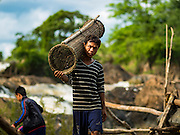 17 JUNE 2016 - DON KHONE, CHAMPASAK, LAOS: A fisherman carries a fish trap to a canoe near Khon Pa Soi Waterfalls, on the east side of Don Khon. It's the smaller of the two waterfalls in Don Khon. Fishermen have constructed an elaborate system of rope bridges over the falls they use to get to the fish traps they set. Fishermen in the area are contending with lower yields and smaller fish, threatening their way of life. The Mekong River is one of the most biodiverse and productive rivers on Earth. It is a global hotspot for freshwater fishes: over 1,000 species have been recorded there, second only to the Amazon. The Mekong River is also the most productive inland fishery in the world. The total harvest of fish from the Mekong is approximately 2.5 million metric tons per year. By some estimates the harvest in the Tonle Sap (in Cambodia) had doubled from 1940 to 1995, but the number of people fishing the in the lake has quadrupled, so the harvest per person is cut in half. There is evidence of over fishing in the Mekong - populations of large fish have shrunk and fishermen are bringing in smaller and smaller fish.        PHOTO BY JACK KURTZ