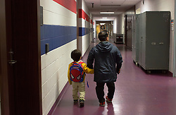 """Brazilian actor Paulo Cesar Oliveira dos Santos walks his son Kauile dos Santos, 7, to school inside the arena where they were performing in Washington D.C. The school travels with the circus and works from a homeschool curriculum. <br /> <br /> Ringling Bros. and Barnum & Bailey Circus started in 1919 when the circus created by James Anthony Bailey and P. T. Barnum merged with the Ringling Brothers Circus. Currently, the circus maintains two circus train-based shows, the Blue Tour and the Red Tour, as well as the truck-based Gold Tour. Each train is a mile long with roughly 60 cars: 40 passenger cars and 20 freight. Each train presents a different """"edition"""" of the show, using a numbering scheme that dates back to circus origins in 1871 — the first year of P.T. Barnum's show."""