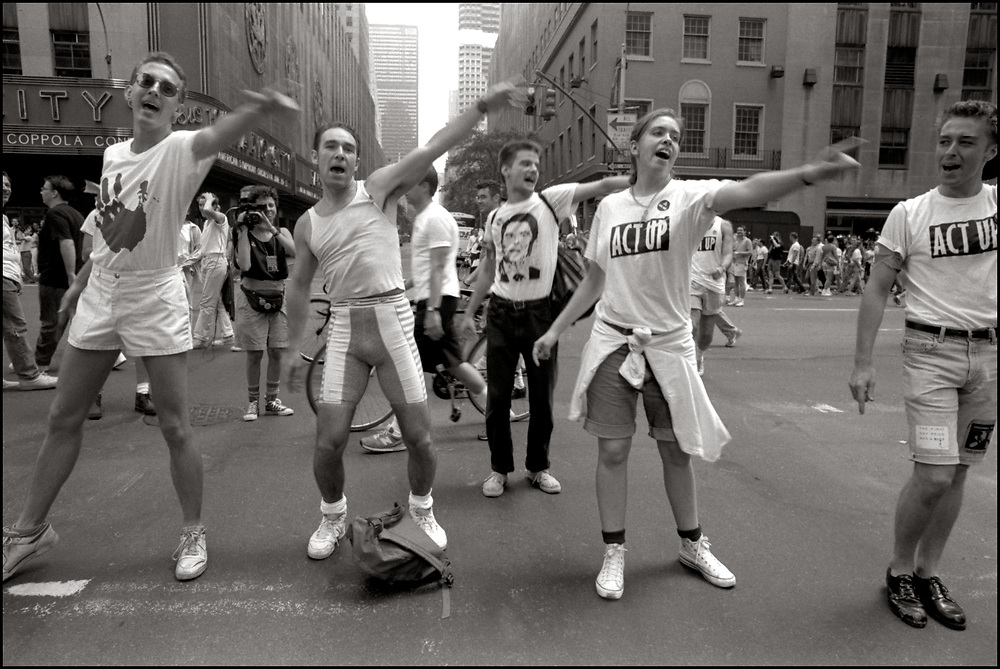"""G'dali Braverman, Darren Jurmé Allumiér, Jean Carlomusto and others, of ACT UP NY, on June 24, 1989, the 20th anniversary of the Stonewall riots, participating in a renegade march up 6th avenue to Central Park. Themed, """"In The Tradition"""", this march followed the same route as the original march 20 years ago and was designed as a rebuke to the corporatization of the gay pride parade. Chanting """"2-4-6-8 How do you know the Rockettes are straight?!?"""" as they passed by Radio City Music Hall."""