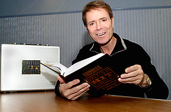 Sir Cliff Richard autographs a special edition of the Guinness book of Hit Singles back stage at the Hallam FM arena on the 8th November 2002<br /> <br /> Image Copyright Paul David Drabble<br /> www.pauldaviddrabble.co.uk