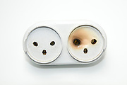 Cutout of a burnt electrical socket on white background