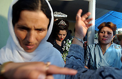 KABUL,AFGHANISTAN - AUGUST 29: An Afghan bride leaves her house with the Holy Koran carried over her head during an engagement ceremony, August 30, 2002 in Kabul, Afghanistan. Each Friday, every beauty salon is filled with  brides, the hotels are jammed with young couples and most streets are packed with streams of cars, blaring their horns as Afghans rush to get married after decades of war. (Photo by Ami Vitale/Getty Images)