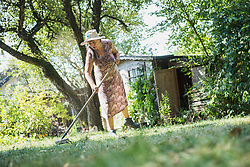 Senior woman raking up the leaves in a garden, Altoetting, Bavaria, Germany