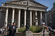 City workers in front of the Victorian columns of the Royal Exchange, enjoy sunshine in Bank Triangle during an unusual autumn heatwave on 13th September 2016, in the City of London, England.