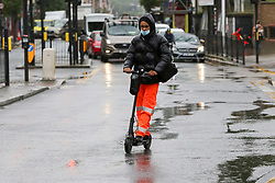 © Licensed to London News Pictures. 21/06/2021. London, UK. A man on an electric scooter in wet weather in north London. Photo credit: Dinendra Haria/LNP