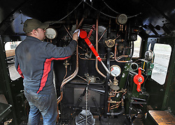 ©London News pictures. 30/03/2011. A worker cleans the interior ahead of the launch. The King Edward II steam locomotive is moved from her protective shed at the Railway Centre in Oxfordshire, England, on 30th March 2011, ahead of her public unveiling this weekend. A small group of volunteer workers met every two weeks and completed the restoration of the engine, once destined for the scrap heap, after 20 years. King Edward II is a Great Western Railway (GWR) heavy express steam locomotive, one of only three surviving members of this class of locomotive. King Edward II performed over 1,500,000 miles of service pulling trains between London Paddington and the West of England, and also in latter years between Paddington and South Wales or Wolverhampton. Introduced in the 1920s for taking express trains over the steep gradients (banks) of South Devon, the Kings were withdrawn in the early 1960s as diesel locomotives replaced them. 6023 spent many years rotting at Barry Scrapyard, and had her rear driving wheels cut through with an oxy-acetylene torch after a shunting accident. . Picture credit should read Stephen Simpson/LNP