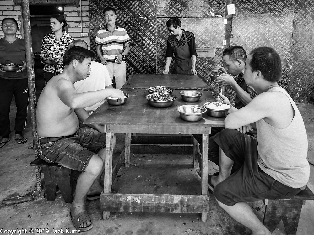 "15 FEBRUARY 2019 - SIHANOUKVILLE, CAMBODIA: A Chinese construction boss (background, striped shirt) talks to Chinese workers eating their lunch about the afternoon's work. There are about 80 Chinese casinos and resort hotels open in Sihanoukville and dozens more under construction. The casinos are changing the city, once a sleepy port on Southeast Asia's ""backpacker trail"" into a booming city. The change is coming with a cost though. Many Cambodian residents of Sihanoukville  have lost their homes to make way for the casinos and the jobs are going to Chinese workers, brought in to build casinos and work in the casinos.     PHOTO BY JACK KURTZ"