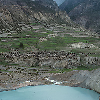 A glacial outflow lake and Manang village lin the remote Manang Valley north of Annapurna in Nepal.