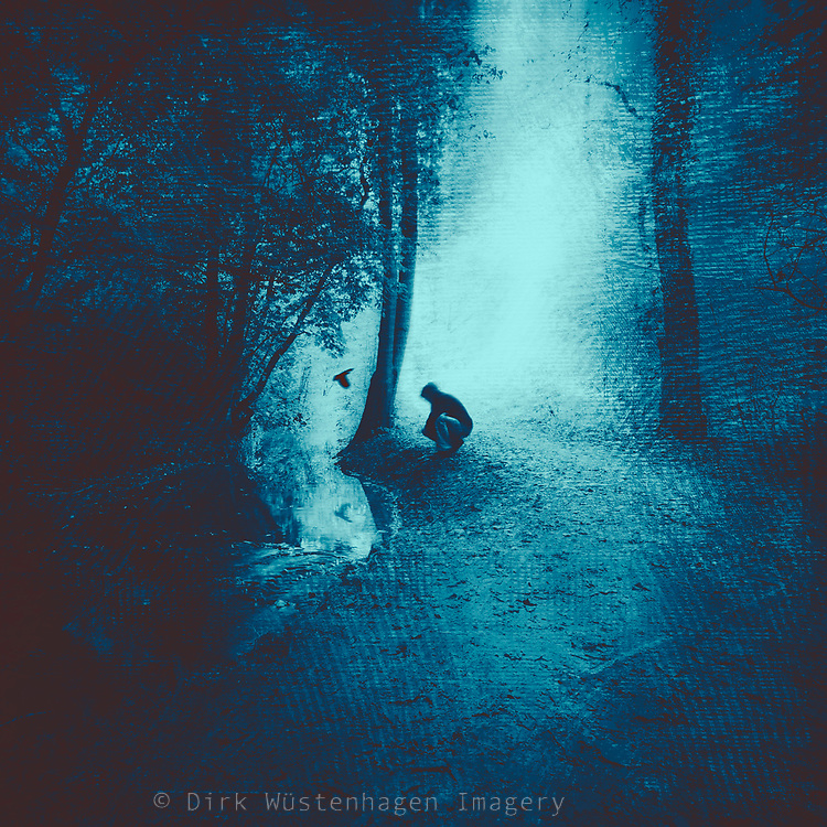 man crouching on the ground - blue tinted and textured photograph