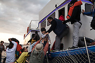 A boat carrying around 150 Syrian refugees lands on the Greek island of Lesvos. People are helped off by volunteers and other refugees.