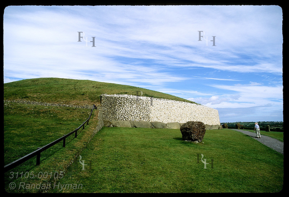 Man leans on cane and admires Newgrange burial mound, a Neolithic (3200 BC) passage grave in Boyne Valley; County Meath, Ireland.