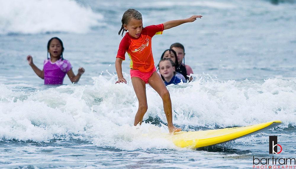 KEVIN BARTRAM/The Daily News.A young surfer rides a wave as other campers watch during the Ohana Surf Camp on Tuesday, July 19, 2005. More than 80 campers gathered near 28th Street and Seawall Boulevard for the third session of the camp. Sessions are also scheduled for August and September.