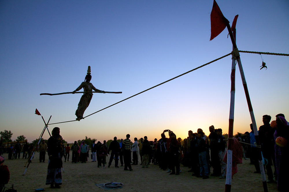 Rajasthan, India. A 12 years old indian girl is performing tightrope walking in front spectators at the Desert Festival in Jaisalmer.<br /> Photo by Lorenz Berna