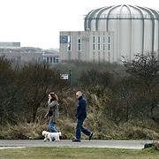 Nederland Petten 7 maart 2009 20090307 Foto: David Rozing ..Kerncentrale Petten, wandelaars laten hond uit.  Nuclear reactor for the production of medical isotopes to treat cancer. Nucleaire onderzoeksreactor, de snelle flux reactor In Petten wordt onder meer onderzoek gedaan naar manieren om de levensduur van radioactief afval te verkorten. Daarnaast worden er medische isotopen gemaakt, die gebruikt worden voor kankerbestrijding. Hoge Flux Reactor (HFR) op het terrein is onderzoeksreactor en levert ook radioactieve preparaten aan de medische sector t.b.v. diagnostiek en radiotherarpie (bestraling, radiofarmacie); voorheen Reactor Centrum Nederland (RCN) / Kerncentrale Petten..Foto: David Rozing