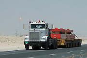 Truck with heavy equipment on a desert highway. Natural gas field in the background.