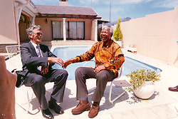 Nelson Mandela sitting around his swimming pool with former prison warden. Picture: THE ARGUS.