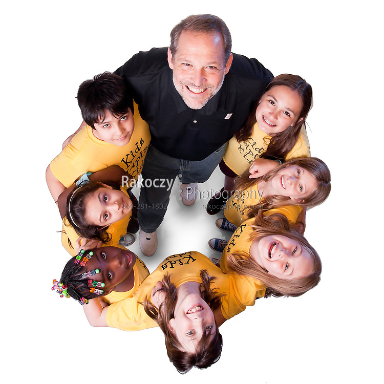 A group of children wearing yellow t-shirts gathered around an adult, looking up, smiling and hugging.