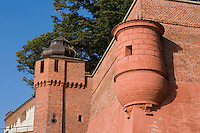 two outlook turrets formed in brick at the wawel castle in krakow poland. the two corner turrets differ in shape - one round, one rectangular. some trees and a blue sky form the background
