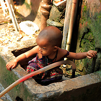 Asia, India, Calcutta. Young girl plays in public water source near the flower market.