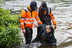 A female anti-HS2 activist tries to stand up after having been pushed by HS2 security guards into the river Colne at Denham Ford during bridge building works for the HS2 high-speed rail link on the first day of the second national coronavirus lockdown on 5 November 2020 in Denham, United Kingdom. Prime Minister Boris Johnson has advised that construction work may continue during the second lockdown but those working on construction projects are required to adhere to Site Operating Procedures including social distancing guidelines to help prevent the spread of COVID-19.