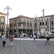 Piazza duomo, sullo sfondo la fontana dell'elefante, conosciuta anche come Liotru, simbolo della città di Catania...Duomo square, in background the elephant fountain, also known as Liotru, the town symbol of Catania.