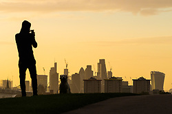 London, September 11 2017. An early morning dog walker uses his smartphone to capture the London skyline as a new day breaks over the city. © Paul Davey